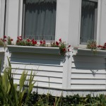 Window box on bay window aluminum sided house.